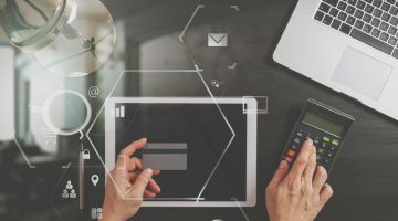 : Draufsicht auf Hände mit Kreditkarte und Taschenrechner auf einem Tisch; daneben Laptop, Tablet, Kaffeetasse und Lampe