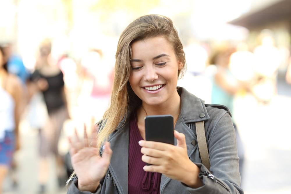 Frau grüßt auf der Straße freudig in ihr Smartphone
